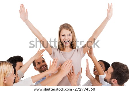She is a real leader. Happy young woman standing against white background and keeping arms outstretched while group of excited people stretching hands to her and smiling - stock photo