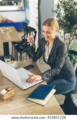 She is always in touch with her clients. Business woman working on laptop in cafeteria