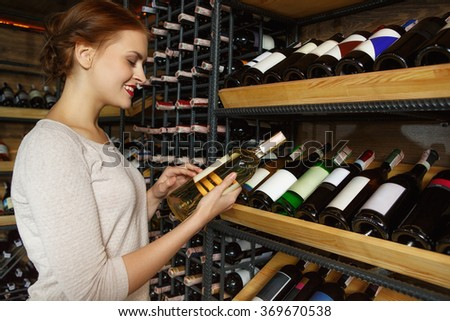 She is an expert! Half length shot of a beautiful young woman shopping in a wine store - stock photo