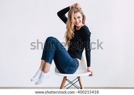 She is simply gorgeous. Beautiful young woman posing and looking away with smile while sitting on chair against white background - stock photo