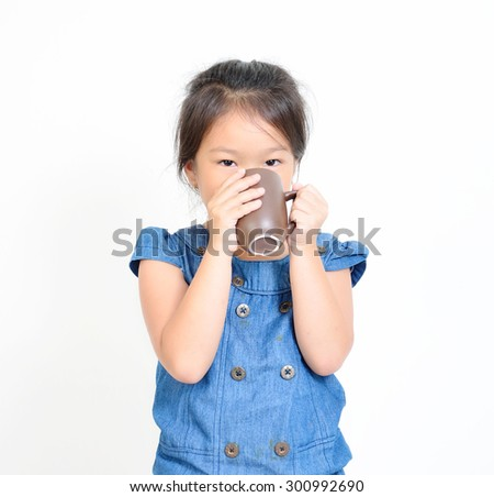 She is sitting on the chair carefully drinking the hot drink. - stock photo