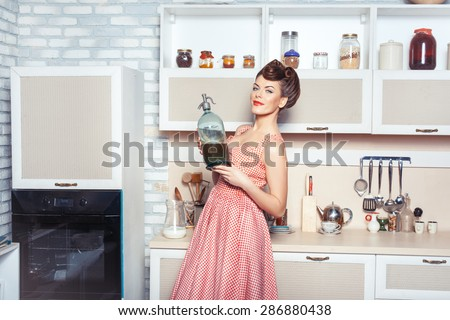 She is the mistress of the kitchen. In her hands she holds a bottle. She smiles. - stock photo
