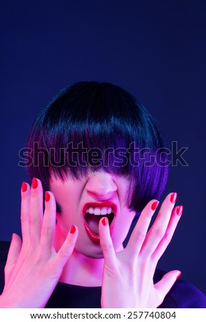 she is very angry. studio dark background - stock photo