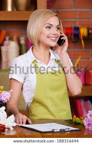 She knows everything about flowers. Beautiful young female florist taking on the phone and smiling while standing at her working place - stock photo