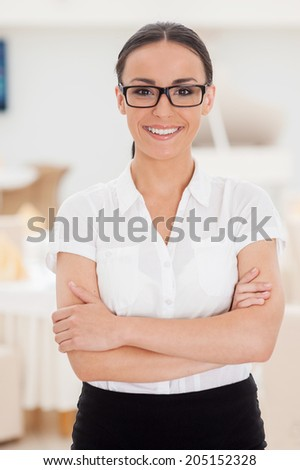 She knows everything about restaurant business. Beautiful young woman in formalwear keeping arms crossed and smiling while standing in restaurant - stock photo