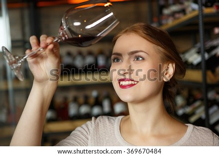 She knows how to choose wine. Closeup shot of a beautiful woman examining glass of wine at the wine store - stock photo