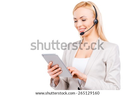 She knows how to help you. Confident mature customer service representative working on digital tablet and smiling while standing against white background - stock photo