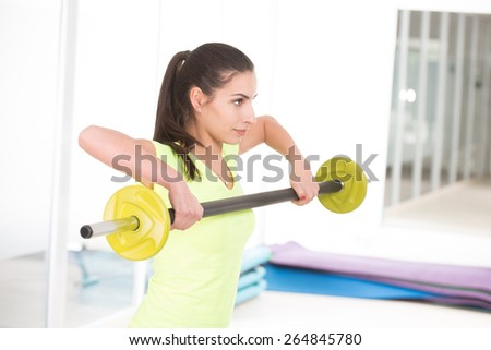 She like to hold barbell. Beautiful sporty woman in gym - stock photo
