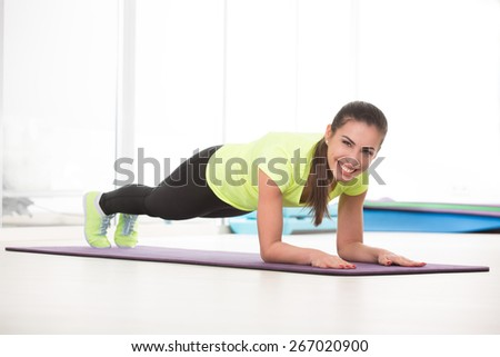 She like to push up on floor. Beautiful woman work hard in gym. - stock photo