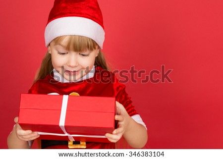 She loves presents. Studio portrait of a little girl wearing Christmas hat and Santa Claus outfit checking out a present holding it in her hands smiling cheerfully  - stock photo