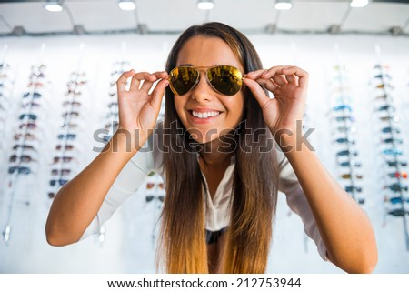 She made her choice. Beautiful young woman adjusting her new sunglasses and smiling while standing in optic store - stock photo
