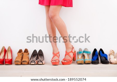 She made her choice. Cropped image of young woman in high heeled shoes standing against the wall while more shoes laying in a row near her - stock photo