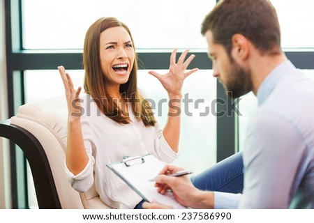 She needs an expert advice. Depressed young woman sitting at the chair and holding hand on head while young man sitting close to her and writing something in his clipboard  - stock photo