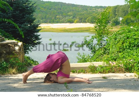 she practices yoga outdoors - stock photo