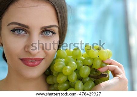 She put a large bunch of ripe green grapes on her left shoulder, and she looks forward. Beauty portrait with bare shoulders and her hair gathered against the glass background
