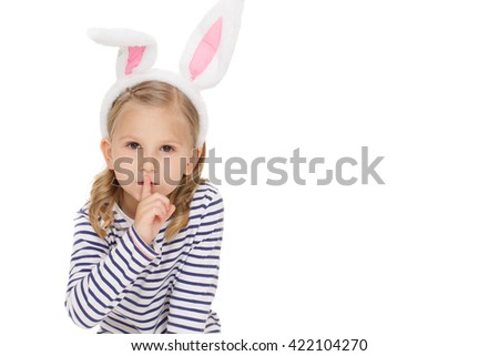 She tells no one. Portrait of beautiful little girl wearing bunny ears looking to the camera making shushing gesture copyspace on the side on white background. - stock photo