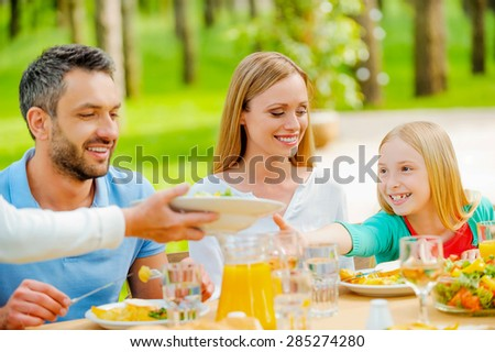 She wants some more salad. Happy family enjoying meal together while sitting at the dining table outdoors  - stock photo