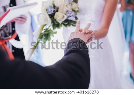 She wears a ring on his finger at the wedding, closeup - stock photo