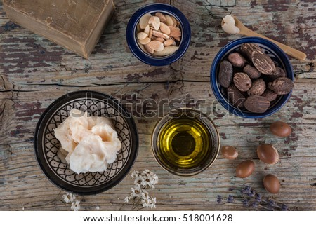 Shea butter and nuts and argan fruits and oil on a wooden table