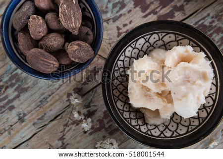 Shea butter and nuts on wood, flat lay