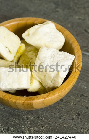 shea butter in bamboo bowl, dark wood table background