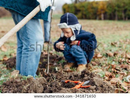 Shears for cutting branches on the ground in front of grandfather and grandson