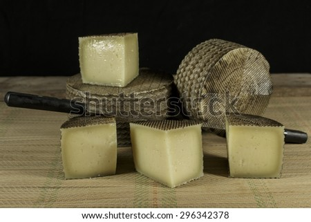 Sheep milk cheeses with double-handled knife - stock photo