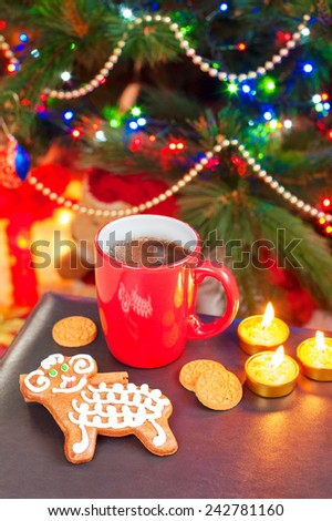 Sheep shape gingerbread with cup of coffee on illuminated christmas tree background. Festive indoors still-life. - stock photo