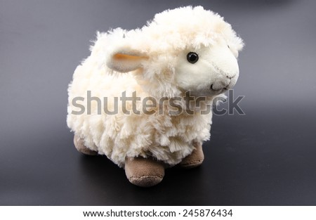sheep toy isolated on a black background - stock photo