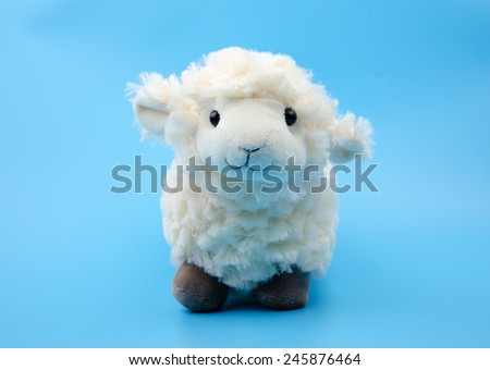 sheep toy isolated on a blue background - stock photo