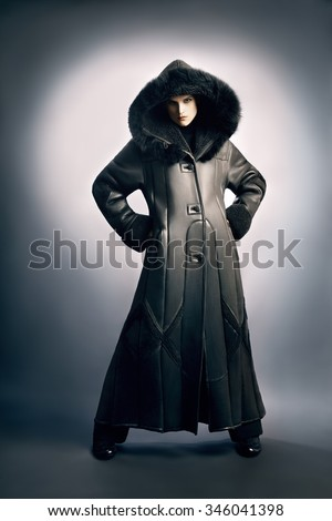 Sheepskin coat winter clothes. Winter fashion woman in long coat with hood cowl