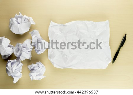 Sheet crumpled paper and a group of crumpled paper balls with black pen on the wooden table background, top view