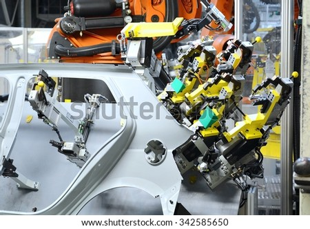 Sheet metal stamped part for the new car in the car factory. The robot holds part for new car. Car factory.  - stock photo