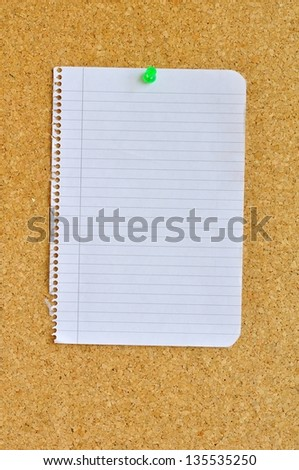 Sheet of notebook pinned with pushpin on cork bulletin board.