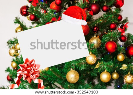 Sheet Of Paper With Bow And Santa Hat On Background Decorated Christmas tree. - stock photo