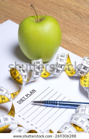 sheet of paper with diet plan, apple, pen and yellow measure tape - stock photo