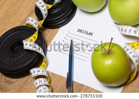 sheet of paper with diet plan, apples and dumbbell on wooden table background - stock photo