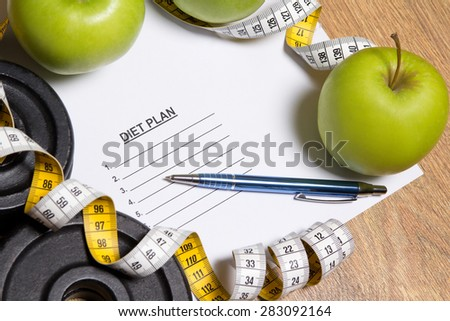sheet of paper with diet plan, apples, dumbbell and measure tape - stock photo