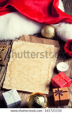 sheet of vintage paper with christmas decoration on wooden background - stock photo