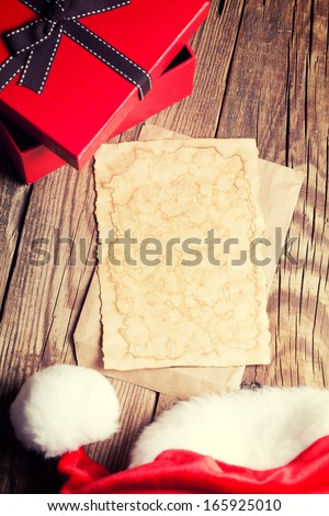 sheet of vintage paper with gift box and santa's hat on wooden background - stock photo