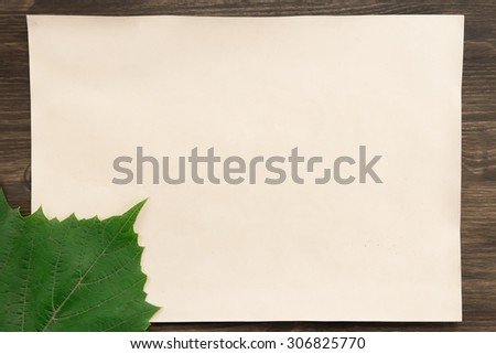sheet old vintage paper with a grape leaf on aged wooden background. Healthy vegetarian food. Recipe, menu, mock up, cooking. - stock photo