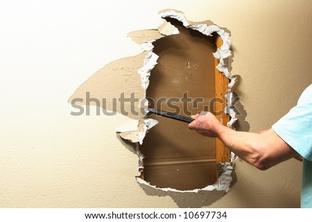 Sheetrock removal. Focus point on hand. - stock photo