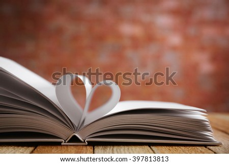 Sheets of book curved into heart shape on unfocused background
