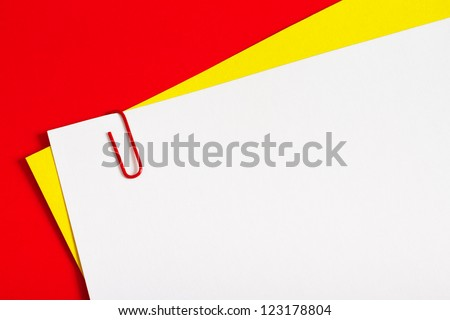 Sheets of color paper connected with red staple on red background - stock photo