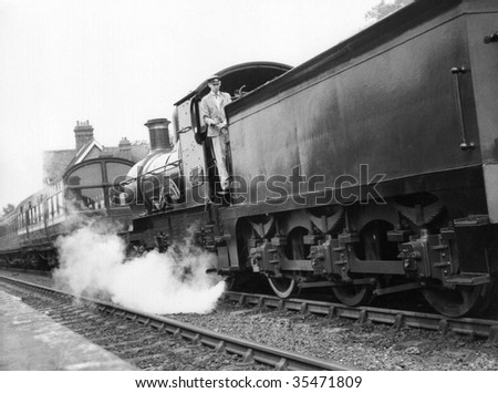 "SHEFFIELD PARK, ENGLAND-CIRCA 1972: A steam locomotive hauls a passenger train on the preserved ""Bluebell Line"" railway circa 1972 in Sheffield Park station, Sussex."