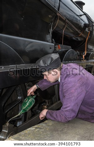 SHEFFIELD PARK, UK - MARCH 19, 2016: Uniformed man pours oil on wheels of a steam engine on The Bluebell Line