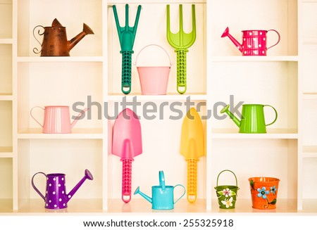 Shelf decoration with colorful gardening tools - watering cans, garden fork, rake, shovel, pail, bucket - stock photo
