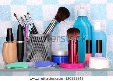 Shelf with cosmetics and toiletries in bathroom - stock photo
