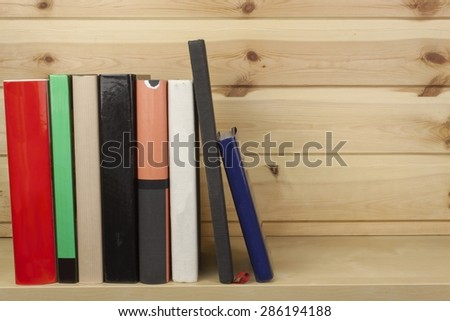 Shelf with different colored books on a wooden background - stock photo
