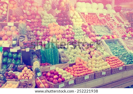 Shelf with fruits on a farm market, trademarks blurred or removed, toned image - stock photo
